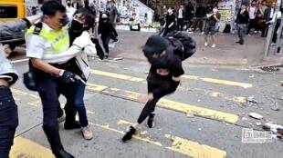 Capture d'écran d'une vidéo montrant un manifestant qui essaie d'empêcher un policier de tirer avec son arme à HongKong, le 11novembre2019.