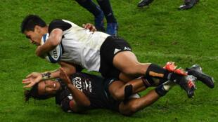 Le Néo-zélandais Rieko Ioane tombe sur l'ailier français Teddy Thomas pendant le match de rugby test France-Nouvelle-Zélande au Stade de France à Saint-Denis, le 11 novembre.