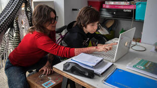 Cinthia Pergola helps her son Francisco during an online class at their home in Sao Paulo, Brazil amid the novel coronavirus pandemic