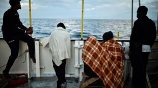 Des migrants observent au loin la côte sicilienne à bord du navire Aquarius, le 14 mai 2018.