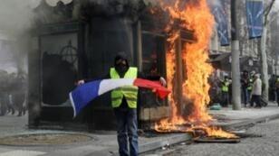 """متظاهر في حركة """"السترات الصفراء""""في جادة الشانزليزيه بباريس في 16 آذار/باريس 2019."""
