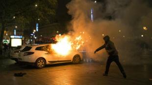 Un véhicule de police incendié par des projectiles, vendredi 22 avril, sur la place de la République, à Paris.