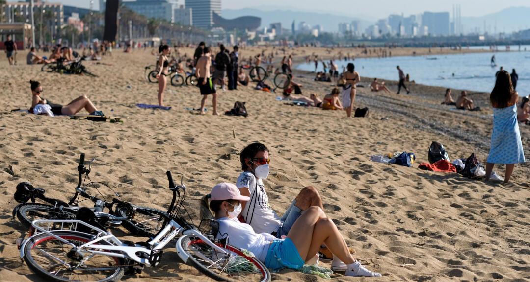 Una pareja con mascarillas disfruta del clima soleado en la playa de la Barceloneta mientras el país vive una etapa de desconfinamiento en medio de la pandemia por coronavirus. Barcelona, España, el 22 de mayo de 2020.