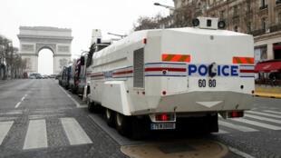Un vehículo de la policía francesa está instalado en la avenida de los Campos Elíseos durante la décima novena protesta nacional consecutiva del movimiento 'chalecos amarillos' en París, el 23 de marzo de 2019