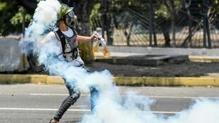 An anti-government protester throws Molotov cocktails during clashes with security forces near the La Carlota military base in Caracas