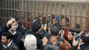 """Defendants react behind the bars at a court in Cairo following the acquittal on January 12, 2015 of 26 men accused of """"debauchery"""" after they were arrested in a night-time raid on a bathhouse in the Egyptian capital last month"""