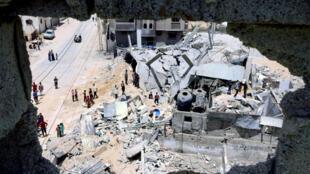 فلسطينيون يتفقدون ما تبقى من منازلهم بعدما دمرتها غارة اسرائيلية في مدينة رفح جنوب قطاع غزة في 16 ايار/مايو 2021