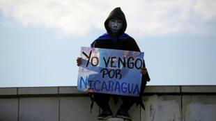 """Un manifestante enmascarado sostiene un letrero que dice """"Vine por Nicaragua"""" durante una manifestación contra el gobierno del presidente Daniel Ortega en Managua, Nicaragua el 18 de mayo de 2018."""