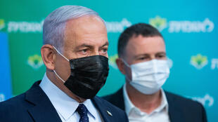 Israeli Prime Minister Netanyahu (L), pictured Tuesday with Health Minister Yuli Edelstein, hopes his success in vaccine procurement will help him keep his job in upcoming elections