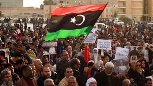 Supporters of Libyan military strongman Khalifa Haftar wave a national flag in a February 2020 demonstration in Benghazi