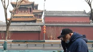 A man wears a face mask as he walks past the closed Lama Temple in Beijing on February 13, 2020.