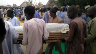 Le corps d'une victime transporté par des habitants du village de Lawanti, au Nigeria, où une attaque avait été perpétrée par Boko Haram en février 2019.