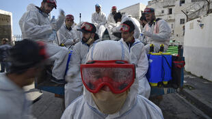 عمال بلديون يرتدون بدلات واقية خلال تعقيم شارع من كوفيد-19 في منطقة باب الواد بالعاصمة الجزائرية، 9 نيسان/أبريل 2020.