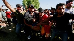 رجال يحملون متظاهرا مصابا في احتجاج أثناء حظر التجول ببغداد، 4 أكتوبر/تشرين الأول 2019.