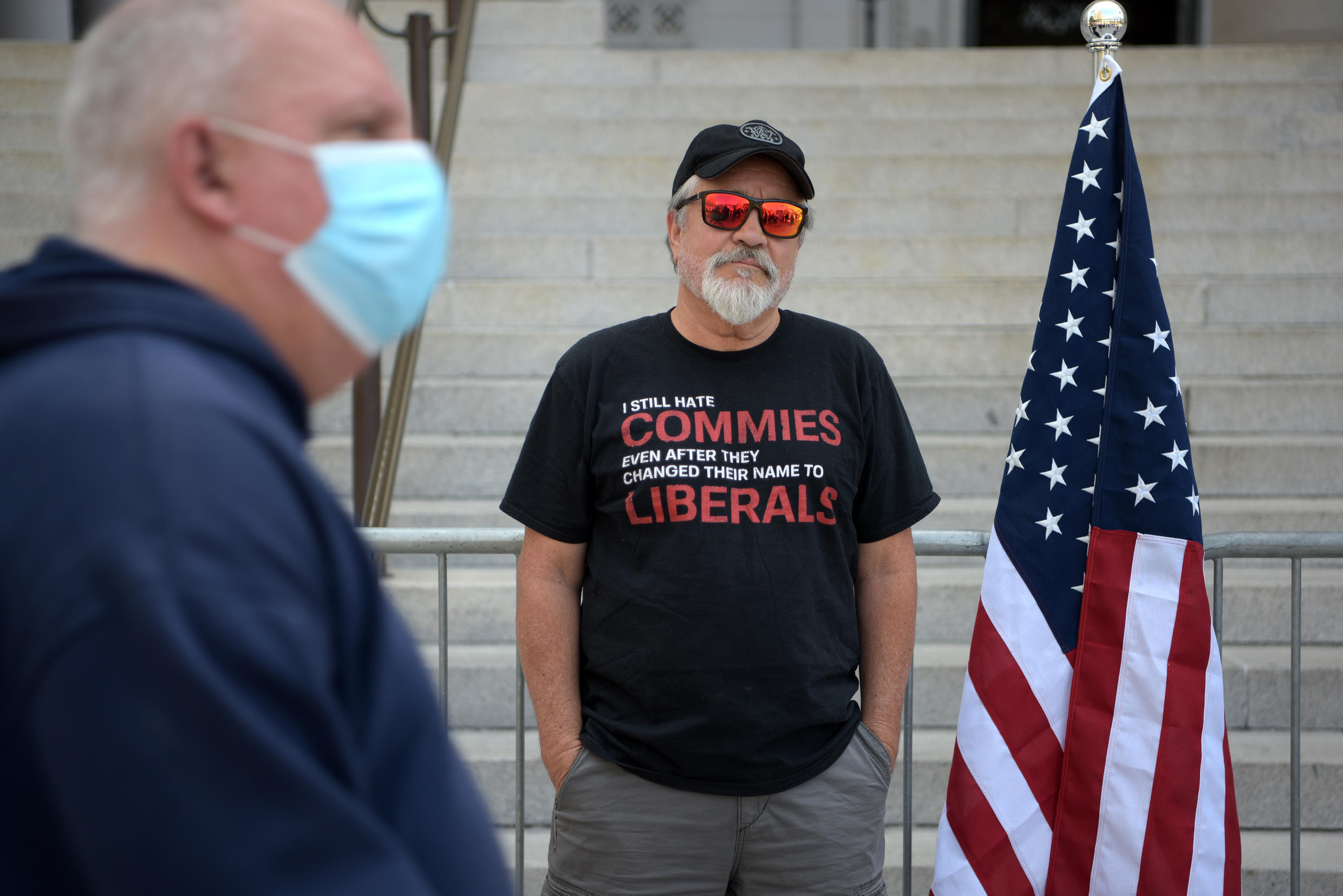 A man wearing a facemask walks past another standing with a US flag during a demonstration against stay-at-home orders near Los Angeles City Hall on May 1, 2020, amid the novel coronavirus pandemic.