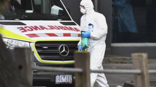 Un hombre con indumentaria protectora pasa junto a una ambulancia estacionada frente a un edificio de viviendas públicas de Melbourne puesto en cuarentena por un brote de coronavirus, el 6 de julio de 2020 en la ciudad australiana