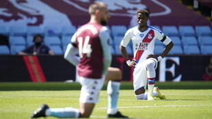 Wilfried Zaha (right)takes a knee prior to Crystal Palace's Premier League match with Aston Villa on Sunday
