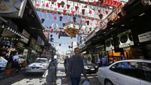 لقطة عامة تظهر متسوقين وسيارات مركونة في سوق الميدان في دمشق في 26 نيسان/أبريل 2020