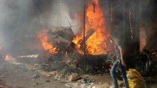 أحد السكان ينظر إلى كشك محترق بعد غارة جوية على سوق في معرة النعمان في محافظة إدلب 8 تشرين الأول/أكتوبر 2017