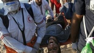 Palestinian demonstrators and paramedics carry a wounded man on a stretcher during a protest calling for an end to the Israeli blockade on Gaza, on a beach in Beit Lahia near the maritime border with Israel, on September 24, 2018