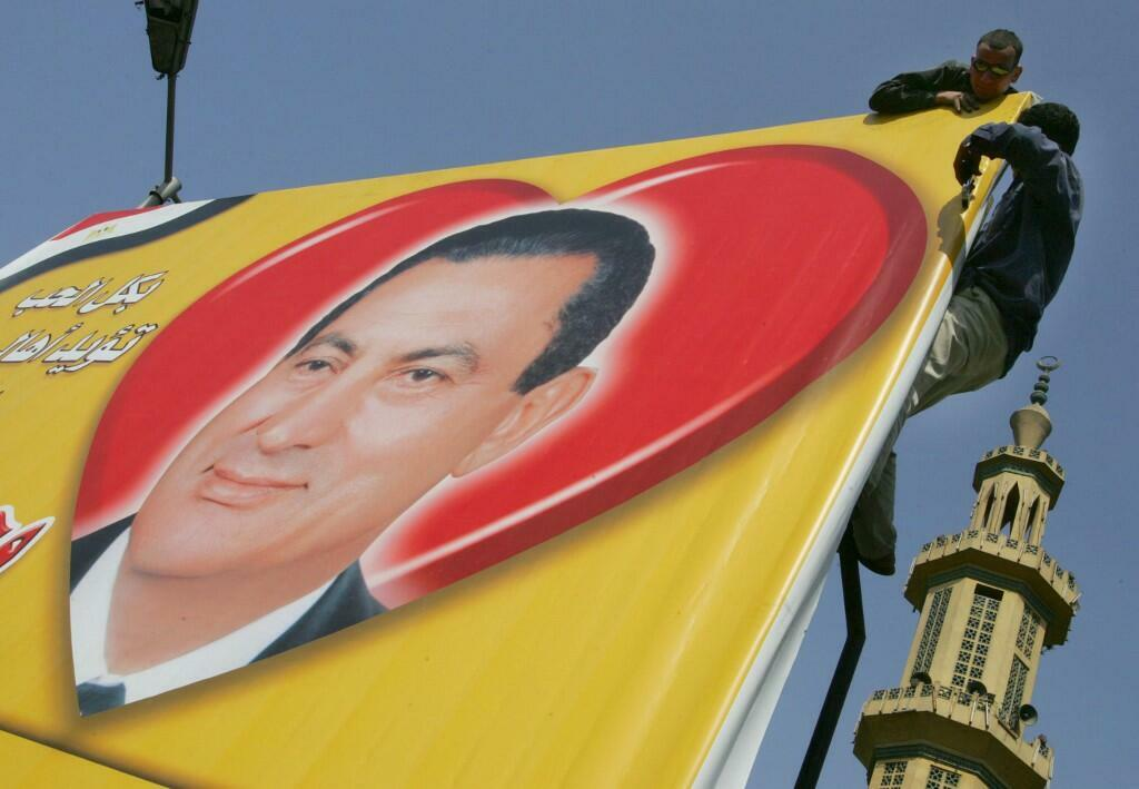 Campaign workers in Cairo add the finishing touches to a billboard ahead of the 2005 Egyptian elections.