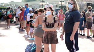 Guests wearing masks wait outside the Magic Kingdom theme park at Walt Disney World on the first day of reopening after it was closed due to the coronavirus pandemic
