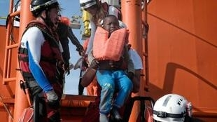 """طفل أثناء إنقاذه في سفينة أكواروس التابعة لمنظمتي """"أس أو أس متوسط"""" و""""أطباء بلا حدود"""" قبالة السواحل الليبية في 12 أيار/مايو 2018."""