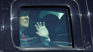 Donald Trump waves from a car as he drives past supporters in West Palm Beach, Florida, on January 20, snubbing his successor's inauguration.