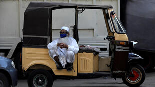 A man sits on the back of his rickshaw as he waits for passengers to offer a ride in Karachi, Pakistan on May 9, 2020, after the country announced the lifting of some Covid-19 lockdown curbs.