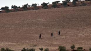 Des combattants de l'organisation de l'État islamique non loin de Kobané, en Syrie, le 18 octobre 2014.