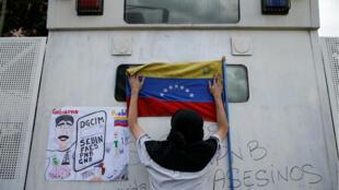 Un partisan de Juan Guaido attache un drapeau lors d'un rassemblement contre le président Nicolas Maduro le jour de la fête de l'indépendance, le 5juillet2019, à Caracas.