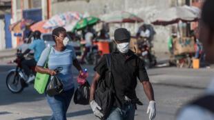 مارة يضعون أقنعة للحماية من فيروس كورونا المستجد في هايتي في 26 آذار/مارس 2020