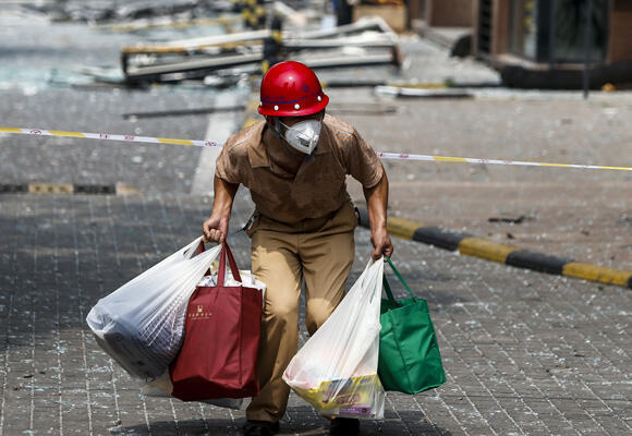 A Tianjin resident carrying his belongings walks out of his home near the site of the explosions. (Photo: STR/AFP)