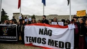 """Striking Portuguese nurses hold a banner that reads """"We are not afraid"""" as they demonstrate outside the Santa Maria central hospital in Lisbon"""