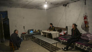 As the battle comes ever closer a family hunkers down to watch television in their basement in Martuni