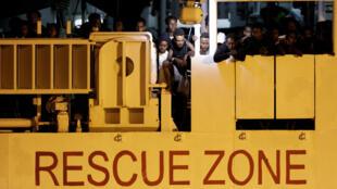"""Archivo: migrantes esperan para desembarcar del bote de la guardia costera italiana """"Diciotti"""", en el puerto de Catania, Italia, el 25 de agosto de 2018."""