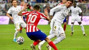 Atletico Madrid's Argentine forward Angel Correa (C) dribbles past Real Madrid's Spanish defender Sergio Ramos (R) during the Spanish Super Cup final between Real Madrid and Atletico Madrid on January 12, 2020, at the King Abdullah Sports City in the Saudi Arabian port city of Jeddah. (Photo by Giuseppe CACACE / AFP)