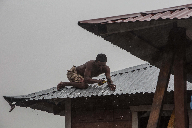 رجل يثبّت سقف منزله في بيلوي في نيكاراغوا في 16 تشرين الثاني/نوفمبر تحسّباً لوصول الإعصار أيوتا