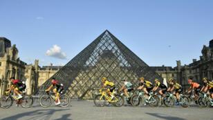 Le Colombien Egan Bernal, vêtu du maillot jaune du leader, avec le peloton de la pyramide du Louvre, le 28 juillet 2019.