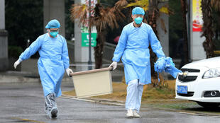 Medical personnel outside a hospital in Wuhan, China, outfitted for coronavirus treatment.