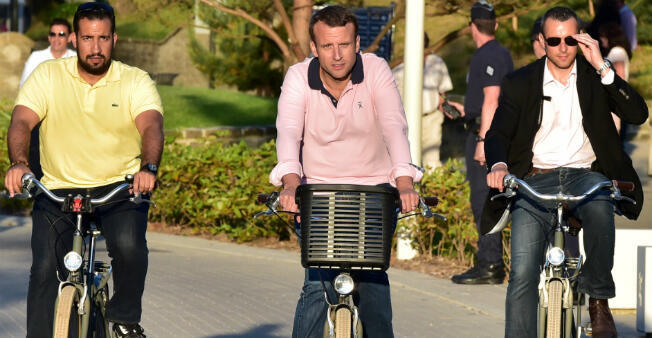 On June 17, 2017 Emmanuel Macron (C) rides a bicycle in the streets of Le Touquet, northern France, accompanied by Élysée senior security officer Alexandre Benalla (L).