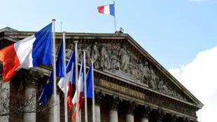 Drapeaux tricolores flottant devant l'Assemblée nationale, à Paris, le 18 juin 2017.