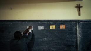 Un empleado electoral camerunés retira las papeletas de voto de un colegio electoral a las afueras de Yaundé, capital de Camerún, el 7 de octubre de 2018