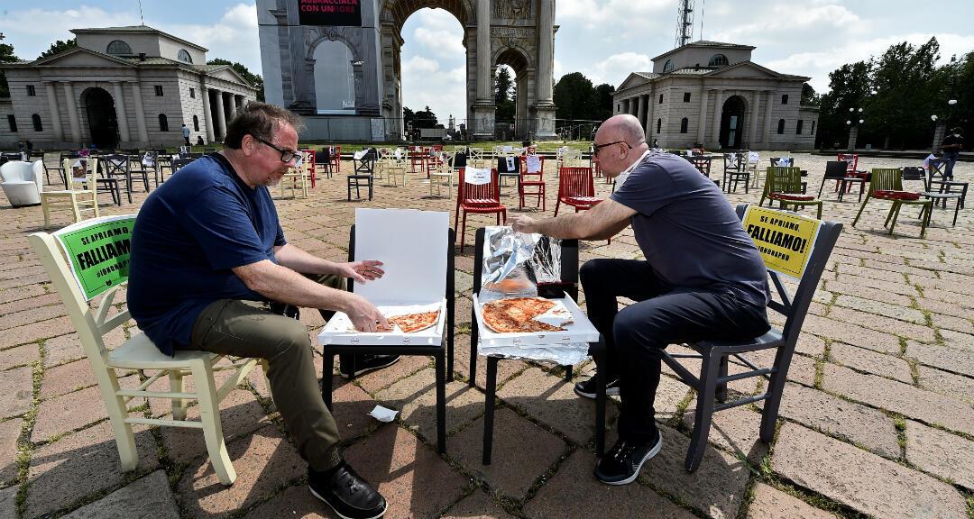 """Los  dueños de dos restaurante comen pizza mientras se sientan en sillas vacías frente al Arco della Pace, como parte de una protesta para exigir más medidas del Gobierno. Tienen letreros que dicen  """"¡Si abrimos, fallamos!"""". Milán, Italia, el 6 de mayo de 2020."""