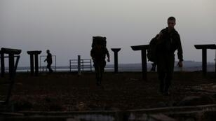Israeli soldiers walk in the Israeli-annexed Golan Heights across the border from the southern Syrian province of Quneitra in July 2018