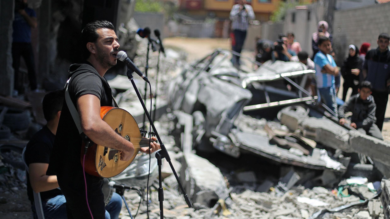 Un cantante palestino actúa durante un evento musical que llama a boicotear el Festival de la canción de Eurovisión organizado por Israel, sobre los escombros de un edificio que fue destruido recientemente por los ataques aéreos israelíes, en la ciudad de Gaza el 14 de