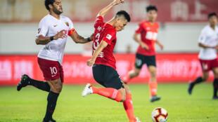 مهاجم شنغهاي سيبغ البرازيلي هولك (يسار) يحاول منع لاعب شنهغاي ايفرغراندي الصيني مي فينغ من التسديد خلال لقاء الفريقين في الدوري الصيني في 23 تشرين الثاني/نوفمبر 2019.