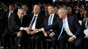 Israel rivals Benjamin Netanyahu and Benny Gantz shake hands as they attend a memorial ceremony for the late prime minister Yitzhak Rabin on November 10, 2019.