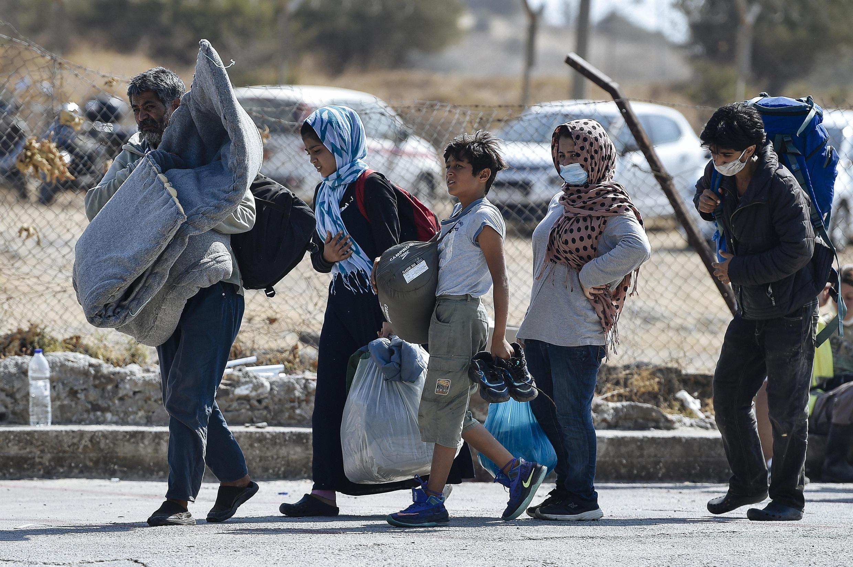 Des migrants se dirigent vers un nouveau camp provisoire, le 13 septembre 2020, après l'incendie qui a ravagé celui de Moria camp, sur l'île grecque de Lesbos.