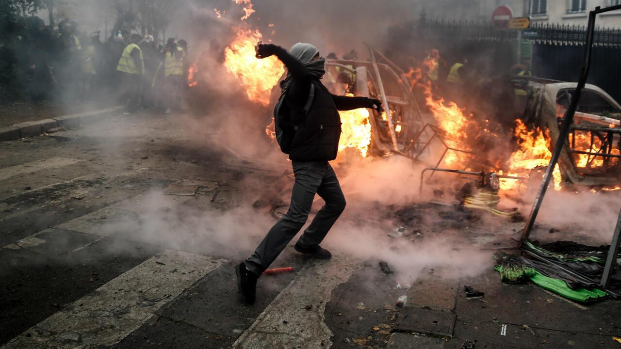 Un manifestant jette un projectile lors d'une manifestation des Gilets jaunes le 1er décembre 2018 à Paris.